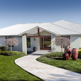 This is an example of a contemporary one-storey white house exterior in Central Coast with a hip roof and a metal roof.