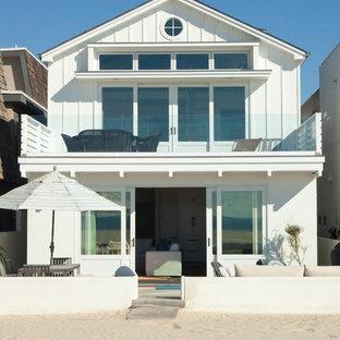 Foto della facciata di una casa piccola bianca stile marinaro a due piani con tetto a capanna e rivestimento in vinile