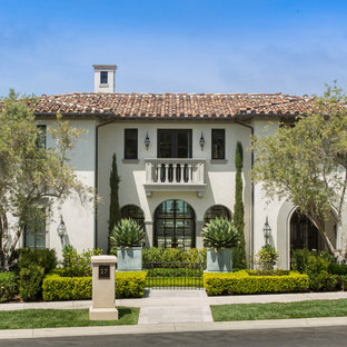 Example of a large tuscan beige three-story stone house exterior design in Orange County with a tile roof and a hip roof
