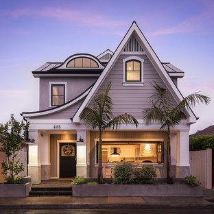 Design ideas for a beach style two-storey grey house exterior in Orange County with wood siding and a metal roof.