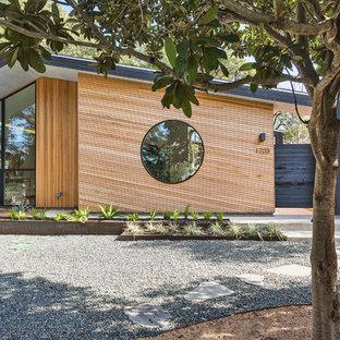 Imagen de fachada negra, minimalista, de tamaño medio, de una planta, con revestimiento de madera y tejado plano