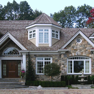 Large traditional beige two-story stone house exterior idea in Boston with a shingle roof