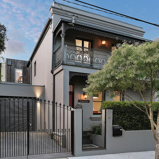 Photo of a large transitional two-storey stucco grey exterior in Sydney with a flat roof.