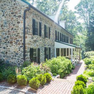 Imagen de fachada de casa de estilo de casa de campo, grande, de tres plantas, con revestimiento de piedra, tejado a dos aguas y tejado de metal