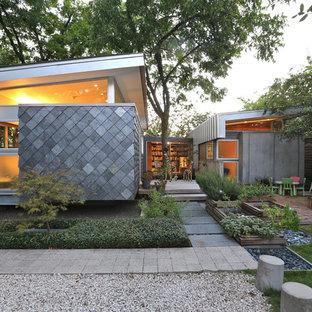 Ejemplo de fachada gris, contemporánea, de una planta, con revestimientos combinados y tejado de un solo tendido