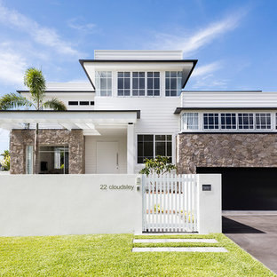 Photo of a beach style two-storey white house exterior in Sunshine Coast.