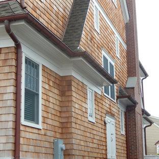 Modelo de fachada de casa beige, costera, de tamaño medio, de tres plantas, con revestimiento de madera, tejado a doble faldón y tejado de teja de madera