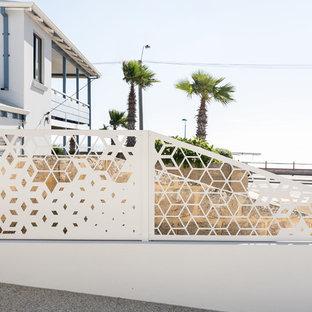 Ejemplo de fachada blanca, marinera, de tamaño medio, de dos plantas, con revestimiento de ladrillo y tejado plano