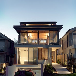 This is an example of a contemporary two-storey glass grey house exterior in Sydney with a flat roof.