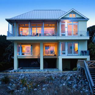 Ejemplo de fachada marinera, de tamaño medio, de dos plantas, con revestimiento de estuco y tejado a cuatro aguas