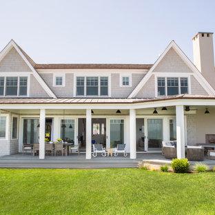 Diseño de fachada de casa beige, marinera, extra grande, de dos plantas, con revestimiento de madera, tejado a cuatro aguas y tejado de teja de madera
