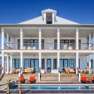 Beach style white two-story exterior home idea in Charleston with a hip roof