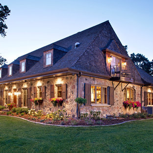 Large french country two-story stone exterior home photo in Minneapolis