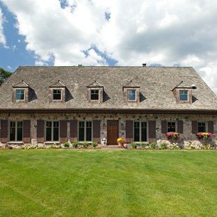 Example of a large french country two-story stone exterior home design in Minneapolis