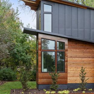 Foto de fachada de casa azul, rústica, de dos plantas, con revestimiento de metal, tejado de un solo tendido y tejado de metal
