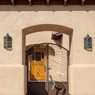 Cette image montre une grand façade de maison beige sud-ouest américain de plain-pied avec un revêtement en stuc, un toit à quatre pans et un toit en tuile.