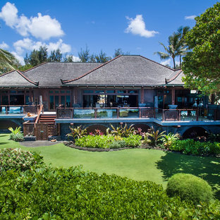 Island style brown house exterior photo in Hawaii with a hip roof and a shingle roof