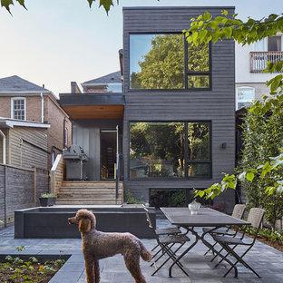 Cette image montre une façade de maison noire nordique à deux étages et plus avec un toit plat.