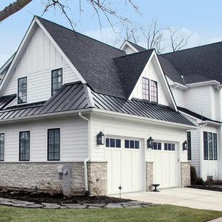 Стильный дизайн: большой, двухэтажный, белый дом в стиле кантри с облицовкой из ЦСП и двускатной крышей - последний тренд