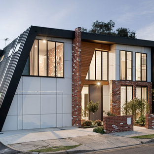 Design ideas for a mid-sized contemporary two-storey exterior in Melbourne with a flat roof and mixed siding.