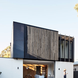 Design ideas for a large contemporary two-storey multi-coloured house exterior in Melbourne with a flat roof and mixed siding.