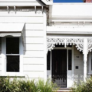 Diseño de fachada blanca, tradicional, pequeña, de una planta, con revestimiento de madera y tejado a dos aguas