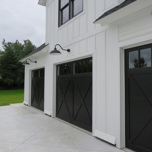 This is an example of a large and white country two floor exterior in Grand Rapids with wood cladding.