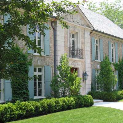 Example of a huge classic beige two-story brick house exterior design in Chicago with a hip roof and a green roof