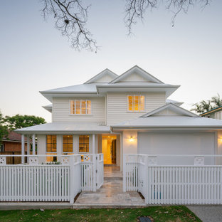 Design ideas for a transitional two-storey white house exterior in Brisbane with a hip roof and a metal roof.
