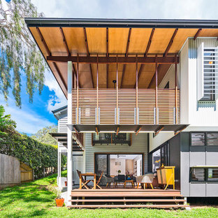 Design ideas for a contemporary two-storey white house exterior in Brisbane with a shed roof.
