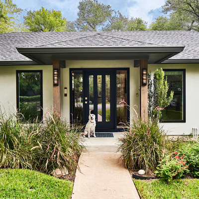 Example of a large 1960s gray one-story stucco house exterior design in Austin with a hip roof and a shingle roof
