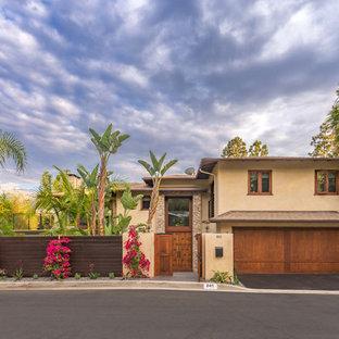 Imagen de fachada de casa beige, exótica, de dos plantas, con tejado a cuatro aguas