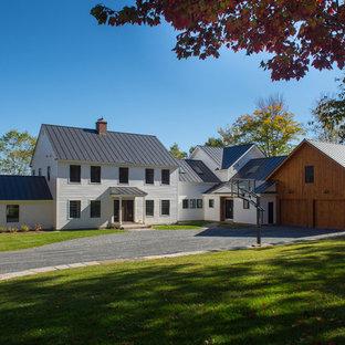 Large farmhouse white two-story vinyl gable roof idea in Burlington