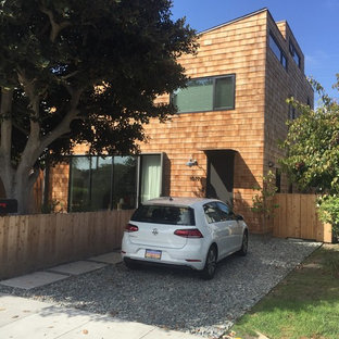 Small minimalist brown three-story wood house exterior photo in Los Angeles with a shed roof and a shingle roof