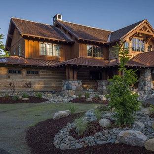 Esempio della facciata di una casa unifamiliare ampia marrone rustica a due piani con rivestimento in legno, copertura mista e tetto a capanna