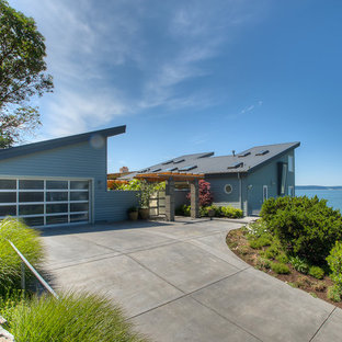 Large minimalist blue two-story concrete fiberboard house exterior photo in Seattle with a shed roof and a metal roof
