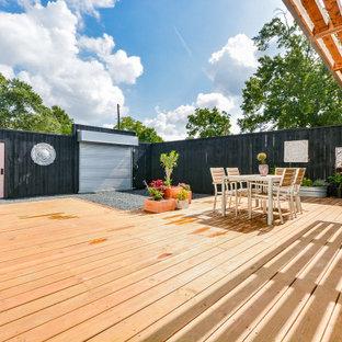 Ejemplo de fachada de casa negra, bohemia, pequeña, de una planta, con revestimiento de aglomerado de cemento, tejado de un solo tendido y tejado de varios materiales