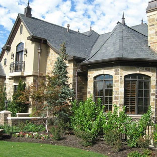 Cottage chic two-story stone house exterior photo in Other with a shingle roof