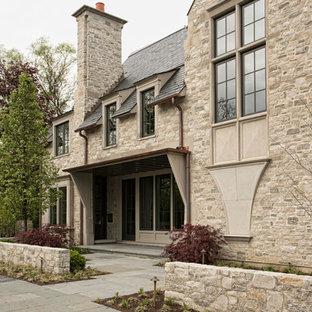 Esempio della facciata di una casa unifamiliare grande beige classica a tre o più piani con rivestimento in pietra e copertura in tegole