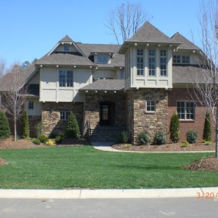 This is an example of a large asian beige exterior in Charlotte with three or more storeys, stone veneer and a clipped gable roof.