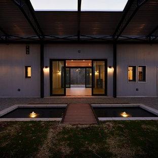Foto della facciata di una casa unifamiliare piccola grigia contemporanea a un piano con rivestimento in metallo, tetto a una falda e copertura in metallo o lamiera