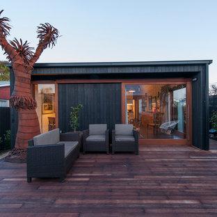 Diseño de fachada de casa negra, contemporánea, pequeña, de una planta, con revestimiento de madera, tejado a dos aguas y tejado de metal