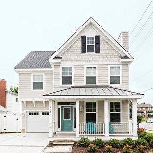 Imagen de fachada de casa beige, costera, grande, de dos plantas, con revestimiento de vinilo, tejado a dos aguas y tejado de teja de barro