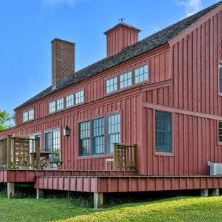 Ejemplo de fachada de casa roja, campestre, grande, de dos plantas, con revestimiento de madera, tejado a dos aguas y tejado de teja de madera
