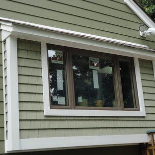 Ejemplo de fachada verde, campestre, grande, con revestimiento de vinilo y tejado a dos aguas