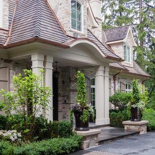Idéer för ett stort klassiskt beige stenhus, med två våningar