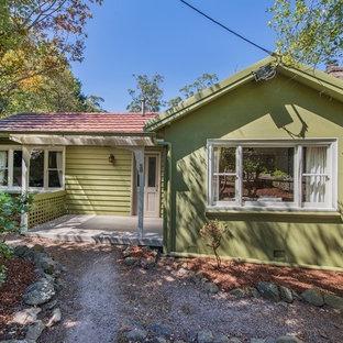 Imagen de fachada de casa verde, campestre, de tamaño medio, de una planta, con revestimiento de madera, tejado a dos aguas y tejado de teja de barro