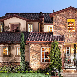 Inspiration for a large mediterranean beige two-story stone exterior home remodel in Los Angeles