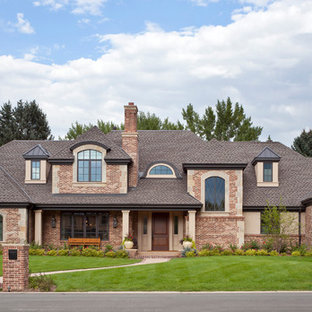 Example of a large classic two-story brick exterior home design in Denver with a hip roof