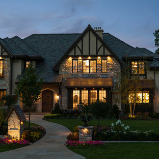 Traditional beige two-story mixed siding house exterior idea in Minneapolis with a hip roof and a shingle roof